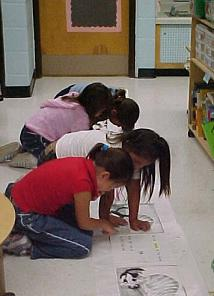 second graders map a scroll on the floor