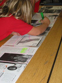 Photograph: Fifth grade girl is actively engaged in the process of marking her scroll.