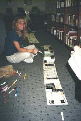 Photograph of a smiling teacher sitting on floor with scroll unrolled in front of her.