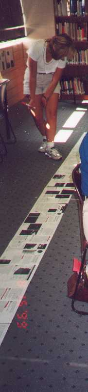 Photograph: Teacher walking along, partially bent over, with a marker in hand, looking down at a scroll that she has unrolled on the classroom floor.